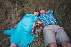 Jeunes couples se trouvant sur l'herbe tenant les mains et le petit chien entre eux Images stock