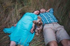 Jeunes couples se trouvant sur l'herbe tenant les mains et le petit chien entre eux Photo libre de droits