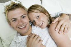 Jeunes couples se trouvant sur la fin de portrait de sofa  Photo stock