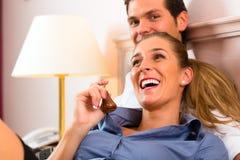 Jeunes couples se trouvant sur le bâti dans la chambre d'hôtel Images libres de droits