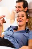 Jeunes couples se trouvant sur le bâti dans la chambre d'hôtel Image stock