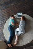 Jeunes couples se trouvant sur le plancher avec l'ordinateur portable et parlant entre eux Image stock