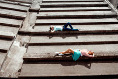 Jeunes couples se trouvant sur le toit gris de l'immeuble dans la recherche photographie stock libre de droits