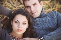 Jeunes couples se trouvant vers le bas souriant au fond d'automne Image stock