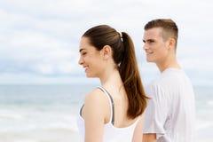 Jeunes couples semblant réfléchis tout en se tenant l'un à côté de l'autre sur la plage Photographie stock