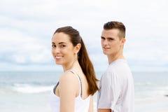 Jeunes couples semblant réfléchis tout en se tenant l'un à côté de l'autre sur la plage Photos libres de droits