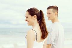Jeunes couples semblant réfléchis tout en se tenant l'un à côté de l'autre sur la plage Photos stock