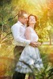 Jeunes couples sensuels dans l'amour extérieur à la lumière du soleil de soirée de fleur avec des fusées Photo stock