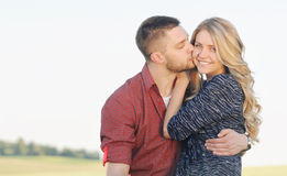 Jeunes couples sensuels dans l'extérieur de baiser d'amour sur le coucher du soleil au su Photos stock