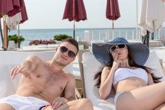 Jeunes couples sexy se reposant sur des chaises longues Photographie stock libre de droits