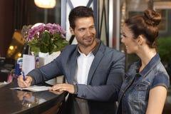 Jeunes couples signant à la réception d'hôtel Images stock