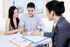 Jeunes couples signant le contrat financier Photographie stock libre de droits