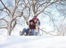 Jeunes couples sledding Photographie stock