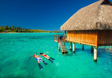 Jeunes couples snorkling de la hutte au-dessus de la lagune tropicale Images libres de droits