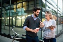 Jeunes couples souriant et employant la technologie dans la ville images stock