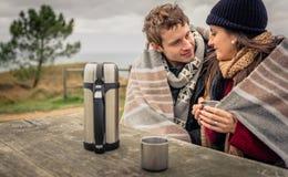 Jeunes couples sous la couverture ayant la boisson chaude dans un jour froid image libre de droits