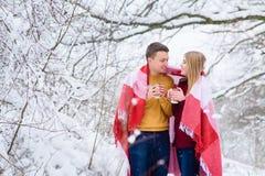 Jeunes couples sous le plaid avec des tasses de thé Photo stock