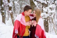 Jeunes couples sous le plaid avec des tasses de thé dehors Photo libre de droits