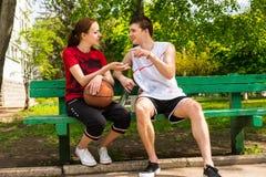 Jeunes couples sportifs ayant la conversation sur le banc Photographie stock libre de droits
