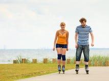 Jeunes couples sur des patins de rouleau montant dehors photo stock