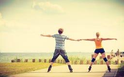 Jeunes couples sur des patins de rouleau montant dehors Image libre de droits