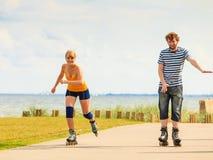 Jeunes couples sur des patins de rouleau montant dehors Image stock