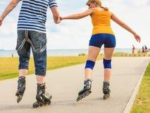 Jeunes couples sur des patins de rouleau montant dehors Photographie stock libre de droits