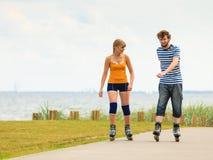 Jeunes couples sur des patins de rouleau montant dehors Images stock