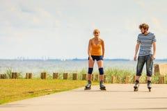 Jeunes couples sur des patins de rouleau montant dehors Photos libres de droits