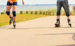 Jeunes couples sur des patins de rouleau montant dehors Photos stock