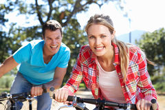 Jeunes couples sur la conduite de vélo de pays Images libres de droits