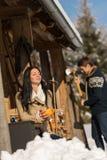 Jeunes couples sur la neige de cottage d'hiver de montagne Photo stock