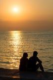 Jeunes couples sur la plage au coucher du soleil Image libre de droits
