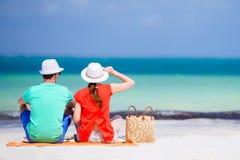 Jeunes couples sur la plage blanche Femme dans le sac rouge de chemise et de plage Image libre de droits