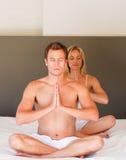 Jeunes couples sur la position de Bouddha sur le bâti Photographie stock libre de droits