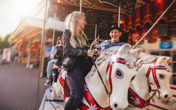 Jeunes couples sur le carrousel de parc d'attractions Photo stock