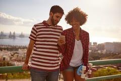 Jeunes couples sur le pont avec le téléphone portable Photo stock