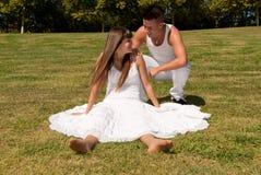 Jeunes couples sur le rapport blanc d'amour d'herbe Photos libres de droits