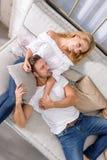 Jeunes couples sur le sofa Photographie stock libre de droits