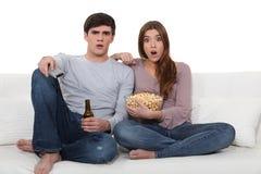 Jeunes couples sur le sofa avec le maïs éclaté et la bière Photographie stock