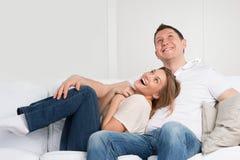 Jeunes couples sur le sofa dans l'amour Images stock