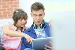 Jeunes couples sur le sofa utilisant le comprimé Images libres de droits