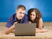 Jeunes couples sur le tapis beige Images libres de droits