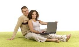 Jeunes couples sur le tapis vert avec l'ordinateur portatif Photo libre de droits