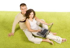 Jeunes couples sur le tapis vert avec l'ordinateur portatif Photos libres de droits