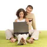 Jeunes couples sur le tapis vert avec l'ordinateur portatif Photographie stock