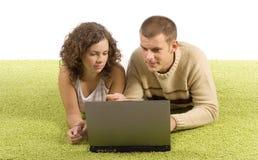 Jeunes couples sur le tapis vert avec l'ordinateur portatif Photos stock