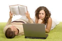 Jeunes couples sur le tapis vert avec l'ordinateur portatif et le livre Photos libres de droits