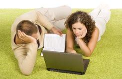 Jeunes couples sur le tapis vert avec l'ordinateur portatif et le livre Image libre de droits