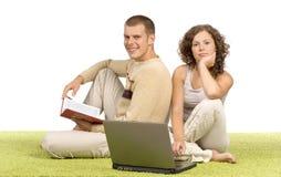 Jeunes couples sur le tapis vert avec l'ordinateur portatif et le livre Photo stock